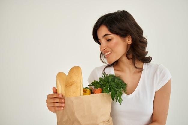식료품 배달과 함께 가방에 흰색 티셔츠를 입은 쾌활한 여자. 고품질 사진