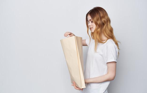 그녀의 손에 패키지와 함께 흰색 티셔츠에 쾌활한 여자 쇼핑