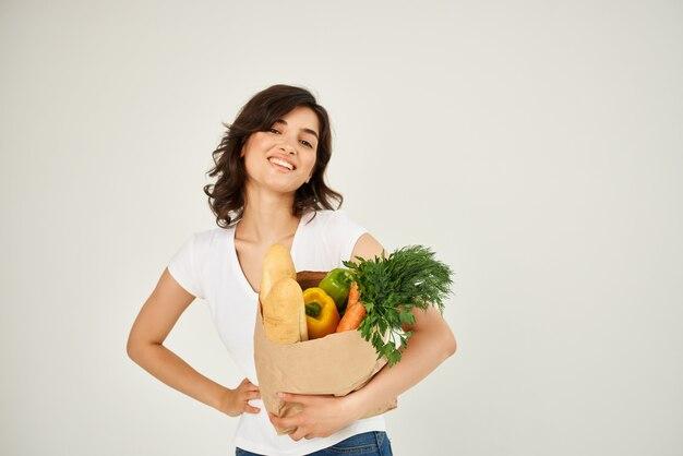 슈퍼마켓 건강에서 식료품과 흰색 tshirt 패키지에 쾌활한 여자