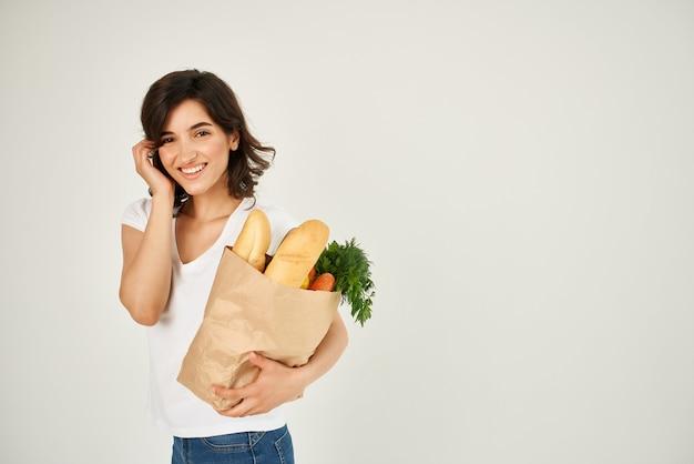 슈퍼마켓 건강에서 식료품과 함께 흰색 티셔츠 패키지에 쾌활한 여자
