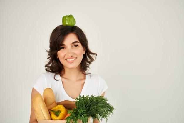 야채 식료품과 함께 흰색 티셔츠 패키지에 쾌활한 여자