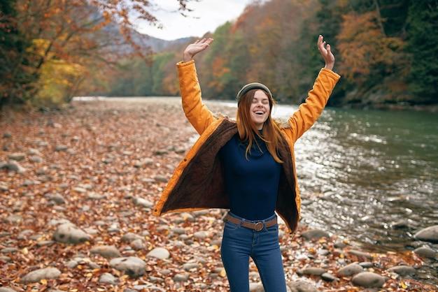 川の秋の散歩の近くの黄色いジャケットの陽気な女性