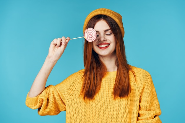 스튜디오 포즈를 취하는 손에 사탕을 들고 노란색 스웨터를 입은 쾌활한 여성