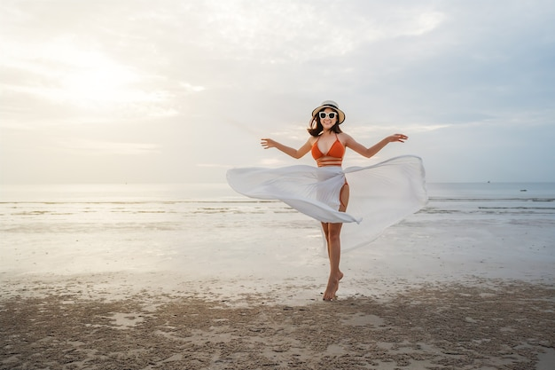 日光の海のビーチで楽しむビキニの陽気な女性