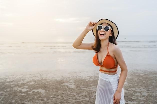 海のビーチで楽しんでいるビキニの陽気な女性