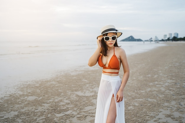 海のビーチに立っているビキニの陽気な女性