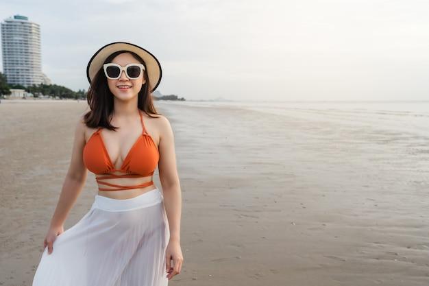 海のビーチを歩くビキニの陽気な女性