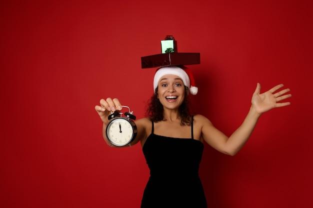검은 이브닝 드레스와 산타 모자를 쓴 쾌활한 여성은 머리에 선물 상자를 얹고 이빨 미소를 지으며 카메라를 보며 밤 12시경 알람 시계를 보여줍니다. 크리스마스 컨셉