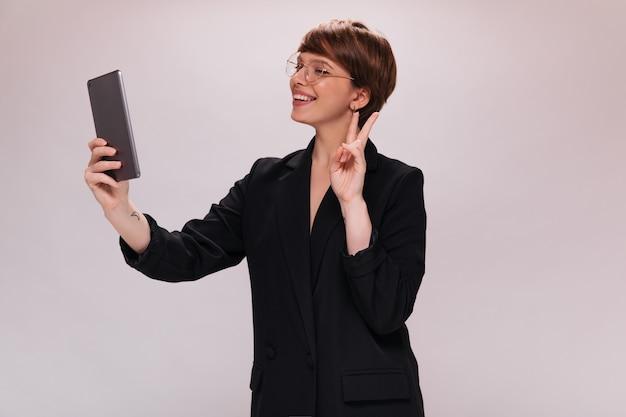黒のスーツを着た陽気な女性は、タブレットを保持し、孤立した背景で自分撮りを取ります。白い背景の上のジャケットの笑顔で幸せな女性