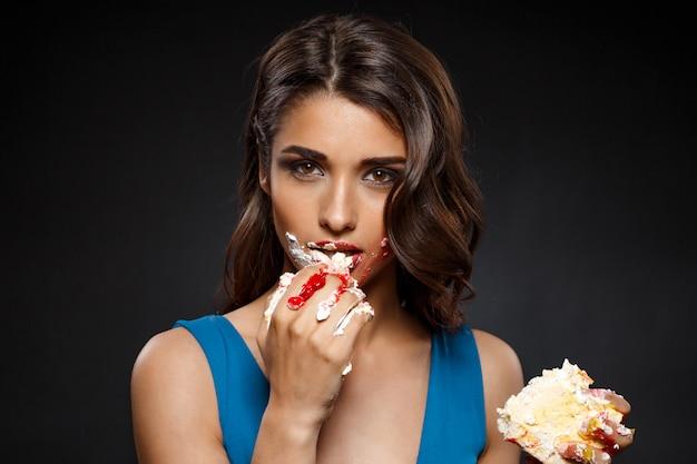 Жизнерадостная женщина в голубом платье ест кусок пирога