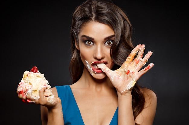 케이크 한 조각을 먹고 파란 드레스에 쾌활 한 여자
