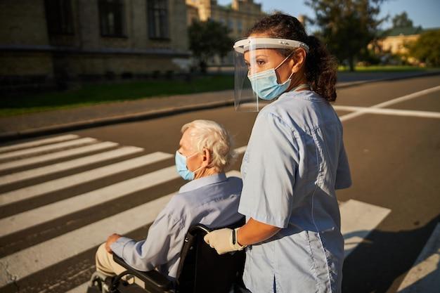 街で年配の男性と一緒に歩いている青い薬の制服を着た陽気な女性