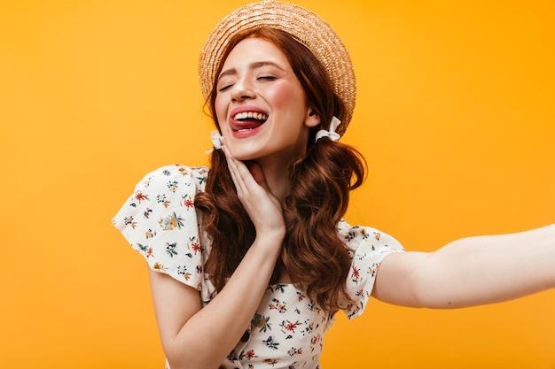 Веселая женщина в канотье показывает язык и позирует для селфи на оранжевом фоне.