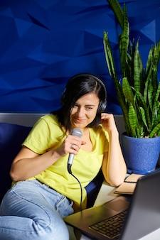 캐주얼 옷을 입은 쾌활한 여성 녹음 팟 캐스트, 헤드폰 및 노트북, 노트북, 여성 팟 캐스터 라이브 스트리밍 또는 노래 노래 부르기로 마이크에 대고 이야기.