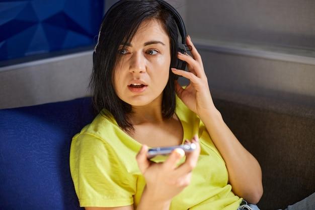 헤드폰과 스마트폰으로 캐주얼 옷을 입은 쾌활한 여성, 팟캐스트에 녹음