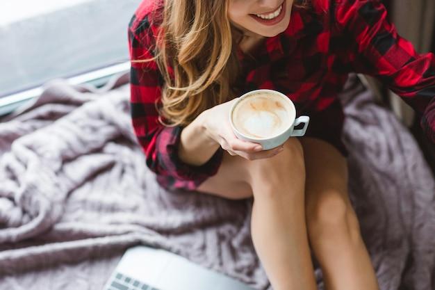 カプチーノを飲む金髪の長い巻き毛とチェッカーシャツの陽気な女性