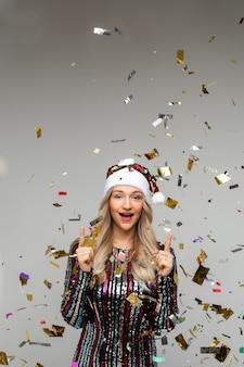 Веселая женщина в платье и новогодней шапке радуется множеству конфетти вокруг нее