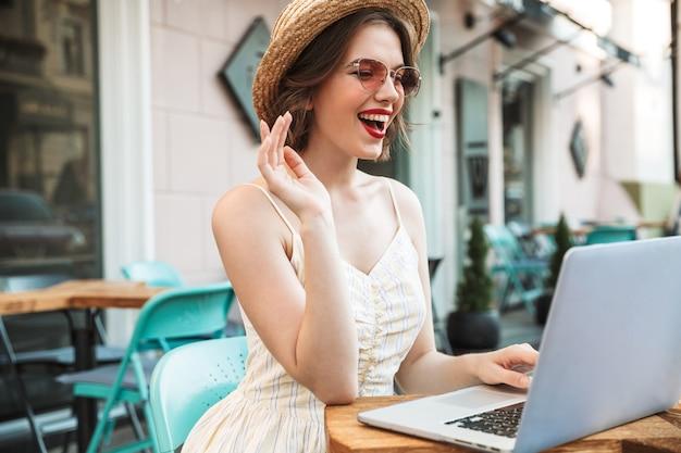 ラップトップコンピューターを使用してドレスと麦わら帽子の陽気な女性