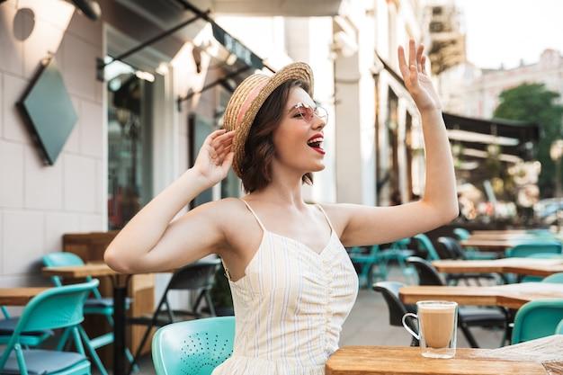 手を振ってドレスと麦わら帽子の陽気な女性