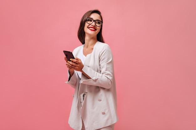Жизнерадостная женщина в очках и бежевом костюме держит смартфон на розовом фоне. улыбающаяся деловая женщина в стильной одежде позирует на камеру.
