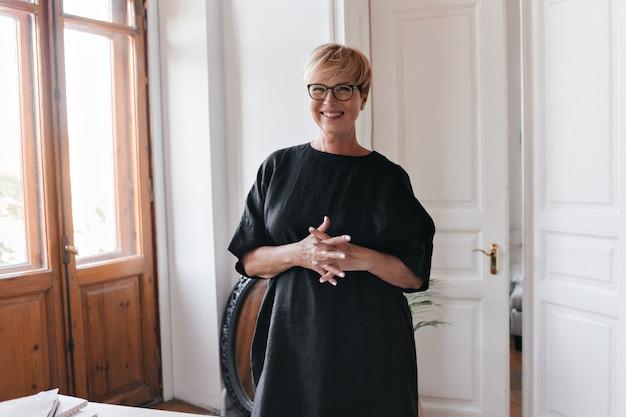 Веселая женщина в очках и платье позирует в офисе