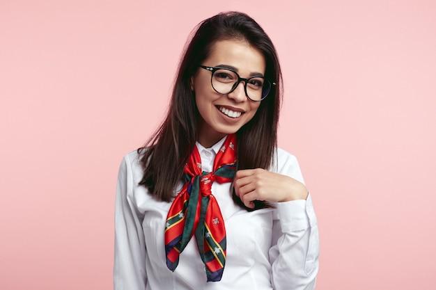 안경에 쾌활한 여자는 분홍색 스튜디오 벽에 행복한 표정을 가지고