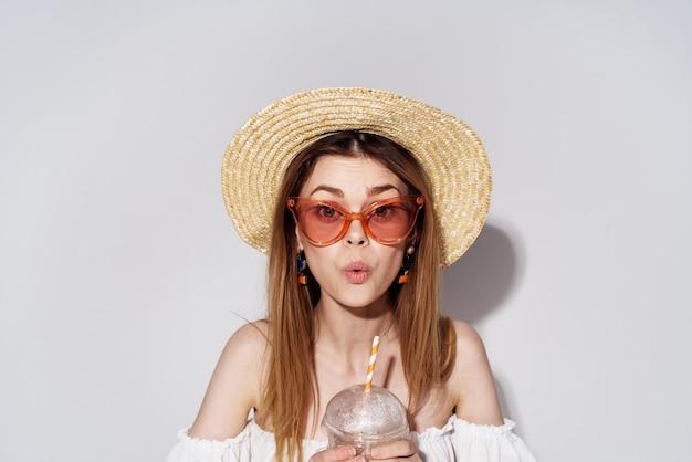 グラスと帽子の陽気な女性が飲み物のクローズアップでチャームグラスを笑顔