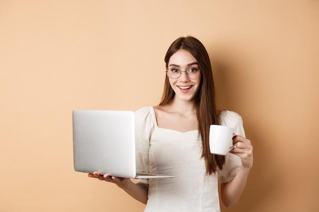 Жизнерадостная женщина в очках пьет кофе и работает на ноутбуке, улыбаясь в камеру, стоя на бежевом фоне.