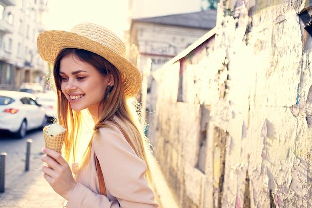 アイスクリームを食べる帽子の陽気な女性は屋外の太陽を歩く