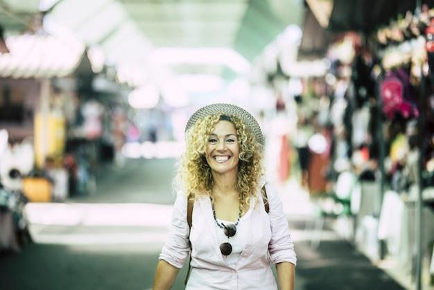 쇼핑을 위해 거리를 걷고 있는 배낭을 메고 모자를 쓴 쾌활한 여자. 흥분에 쇼핑 거리를 걷고 곱슬 머리와 모자에 열정적인 젊은 여자의 초상화