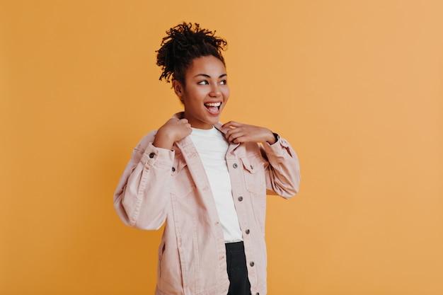 Веселая женщина в куртке, глядя в сторону
