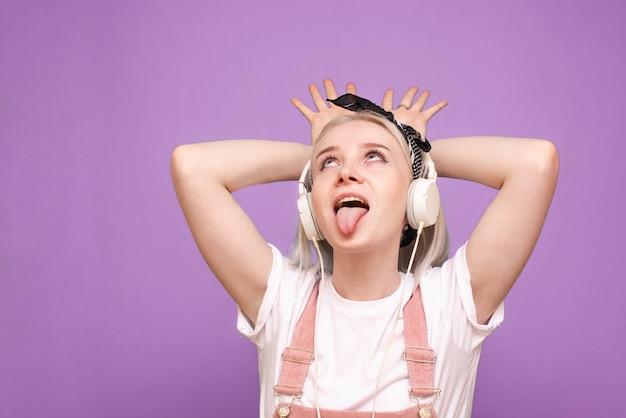 가벼운 옷과 헤드폰에 쾌활한 여자가 재미있는 얼굴을 만든다.