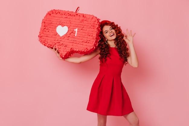 최소한의 빨간 옷을 입은 쾌활한 여자가 미소 짓고 확인 표시를 보여줍니다. 베레모 소녀 핑크 공간에 기호처럼 보유하고있다.