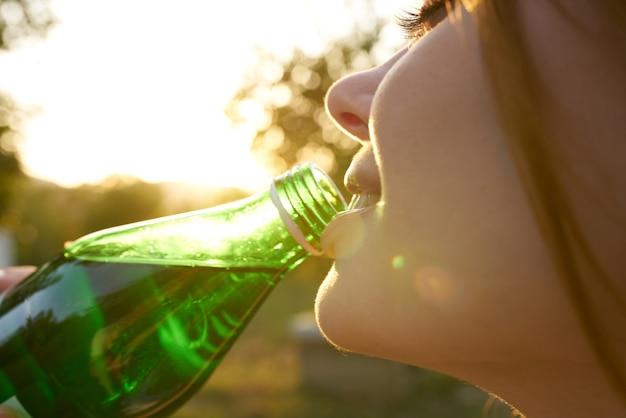 Веселая женщина на природе пьет воду из бутылки освежающего напитка. фото высокого качества