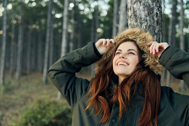자연 속에서 쾌활 한 여자는 야외에서 나무에 그녀의 팔꿈치와 함께 위쪽으로 보인다.