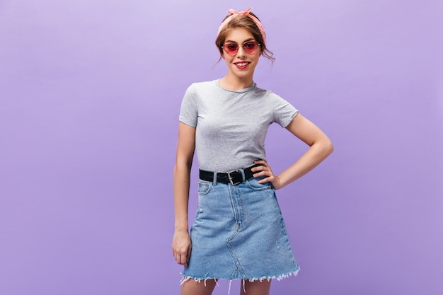 ピンクの眼鏡の陽気な女性は、孤立した背景にポーズをとる。灰色のtシャツとデニムスカートの笑顔のヘッドバンドを持つ素晴らしい女の子。
