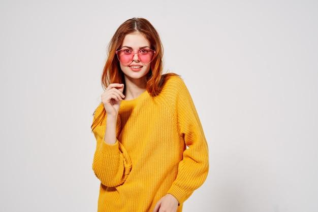 Жизнерадостная женщина в розовых очках, жестикулируя руками студии желтый свитер. фото высокого качества