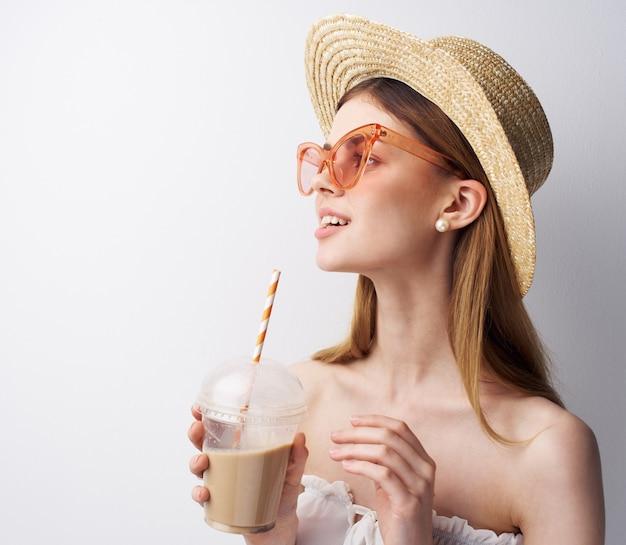 음료 재미와 분홍색 안경 모자 유리에 쾌활 한 여자 모델.