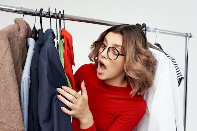 Веселая женщина в красном платье шопоголик выбирает одежду, делая покупки в магазине светлом фоне
