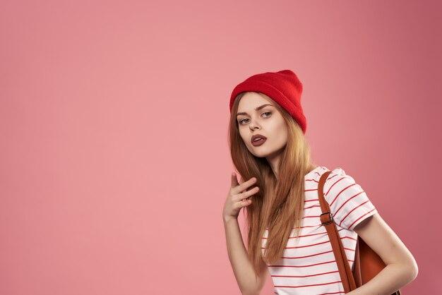 赤い帽子のサングラスファッションピンクの背景の陽気な女性