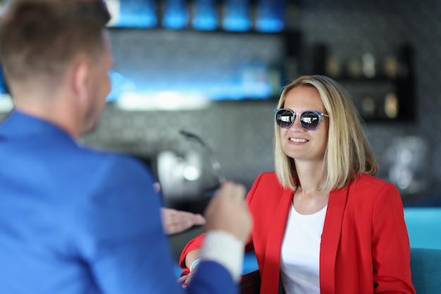赤いジャケットとサングラスで陽気な女性がバーに座っています。