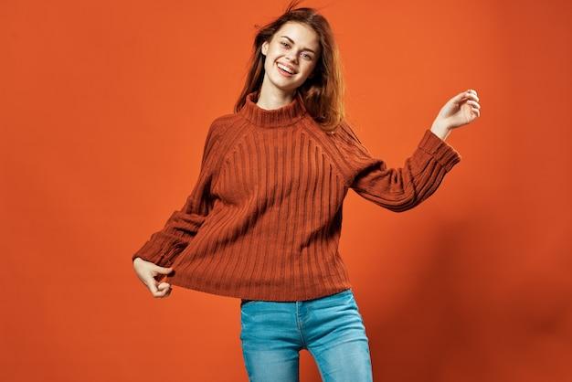 Веселая женщина в красном свитере позирует в студии моды на изолированном фоне