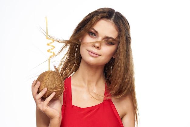 빨간 티셔츠 코코넛 칵테일 이국적인 빛 벽에 쾌활 한 여자.