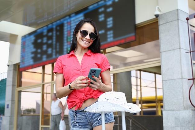 赤いトップの陽気な女性は彼女の手で電話を保持し、オンラインでチケットを購入します。