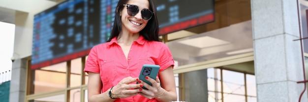 빨간색 상단에 쾌활 한 여자는 그녀의 손에 전화를 잡고 온라인 티켓을 구입합니다.