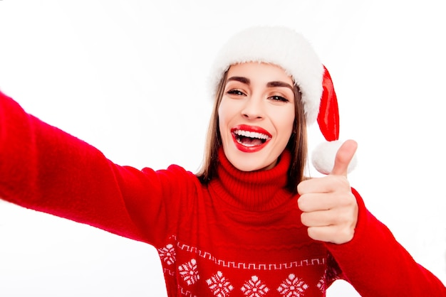 Жизнерадостная женщина в новогодней шапке делает селфи и показывает палец вверх