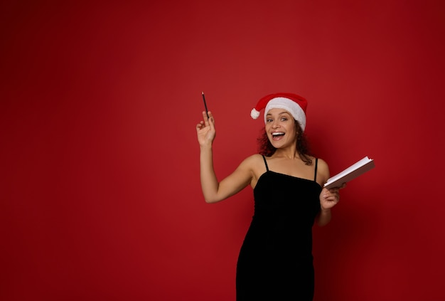 산타 모자를 쓴 쾌활한 여성은 아름다운 이빨 미소로 웃고, 메모장을 들고 카메라를 쳐다보고, 빨간색 배경의 복사 공간에 연필로 가리킵니다. 광고에 대한 크리스마스 및 새해 계획 개념