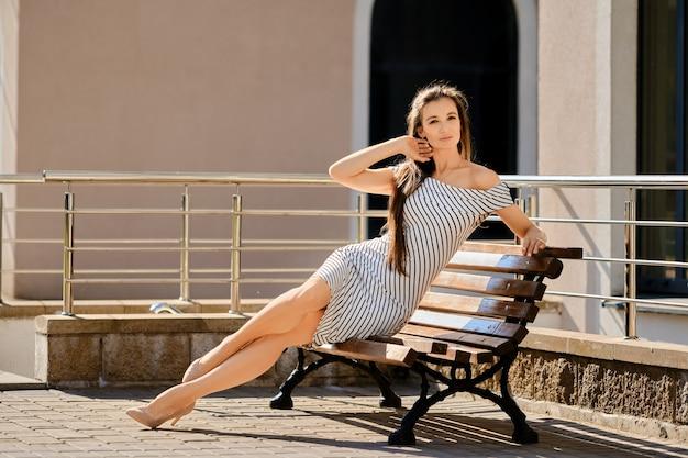 縞模様のドレスを着た陽気な女性が建物の近くの木製のベンチに座って、秋の太陽を楽しんでいます