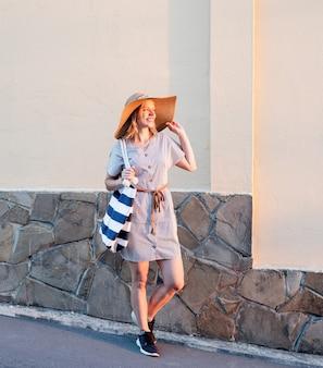 일몰 빛에 그녀의 모자를 들고 거리를 걷고 여름 옷에 쾌활 한 여자