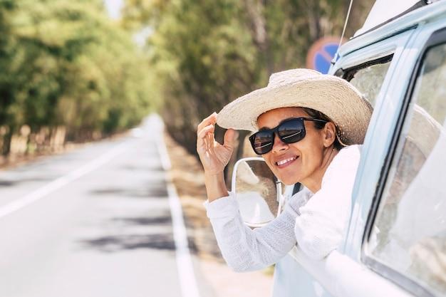 선글라스와 모자를 쓴 쾌활한 여성이 창문에서 차 밖을 바라보고 있습니다. 도 여행에 휴가를 즐기는 젊은 여자. 차창에서 밖을 내다보며 자연을 감상하는 웃는 여자